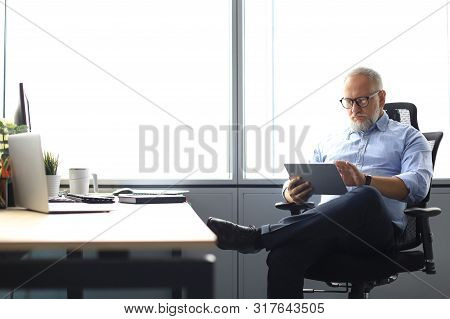 Serious Mature Financial Advisor Sitting At The Table And Checking Financial Report Using Digital Ta