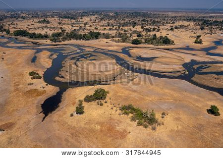 Aerial Of Okavango Delta Watercourse Through Dry Land - Stunning Colorful Landscape In Dry Season