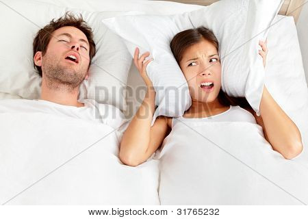Hombre de ronquidos. Pareja en la cama, ronquidos de hombre y mujer no puede dormir, que cubre los oídos con la almohada para el ronquido