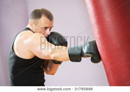 boxer man during boxing hiting heavy bag at training fitness gym poster