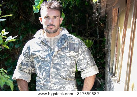 Portrait Of Handsome Male Soldier Wearing Cammies Uniform And Looking At Camera