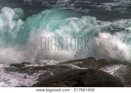 Large Blue Wave Crashing Onto Rocks At Cape Spear, Newfoundland, Canada
