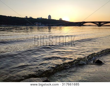 Sunset Over Dnipro River, Ukraine. Beautiful Sunset Background With Bridge And Waves