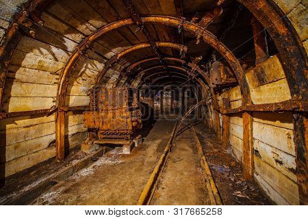Underground Mining Tunnel With Rails. Abandoned Coal Mine. Tunnels And Passages In A Coal Mine.