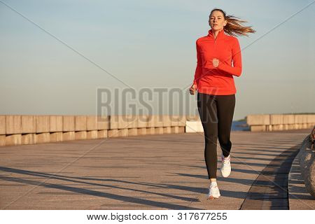 A Jogging Woman In Red Running Shirt And Black Leggins On The Street At Sunrise. Running On Concrete