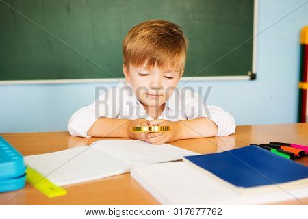 School And Education Concept. Little Children At School Lesson. Happy Student Writing In Notebook In