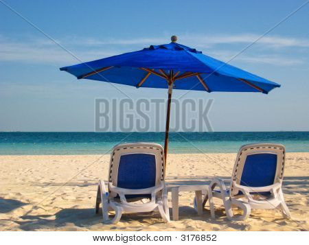 Two Beach Chairs And A Blue Umbrella By The Sea