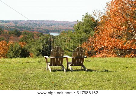 Wooden Adirondack Chairs Overlooking To A Beautiful Fall View Of A Lake And Mountains
