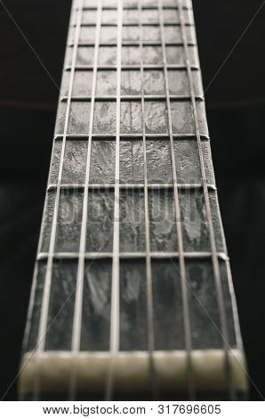 Neck Of A Acoustic Guitar. Details Of The Worn Out Wooden Neck. Neck Of An Old Acoustic Guitar With