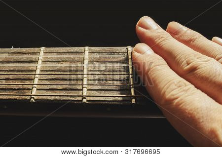 Fingers Muffling The Sound Of The Strings Of An Old Acoustic Guitar, Isolated On A Black Background.
