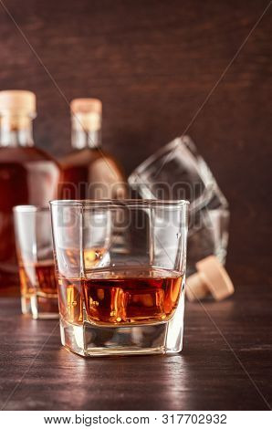 A Glass Of Whiskey With A Double Portion On A Wooden Table. In The Background, Two Bottles Of Whiske