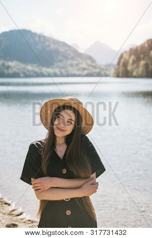 Posing On Camera In The Background Lake And Mountains