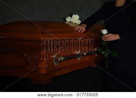 Young Woman With White Rose Near Casket In Funeral Home, Closeup