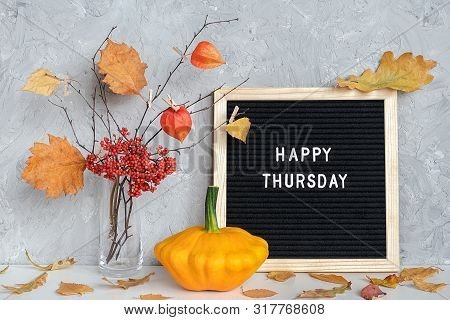 Happy Thursday Text On Black Letter Board And Bouquet Of Branches With Yellow Leaves On Clothespins