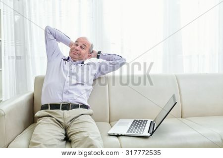 Smiling Lazy Middle-aged Man Sitting On His Sofa And Stretching Back Instead Of Working On Laptop
