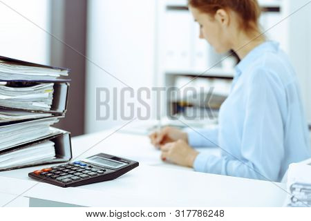 Calculator And Binders With Papers Are Waiting To Be Processed By Business Woman Or Bookkeeper Back