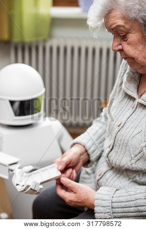 Autonomous Caregiver Robot Is Holding Medication Container Or Pill Box, Giving It To An Senior Adult