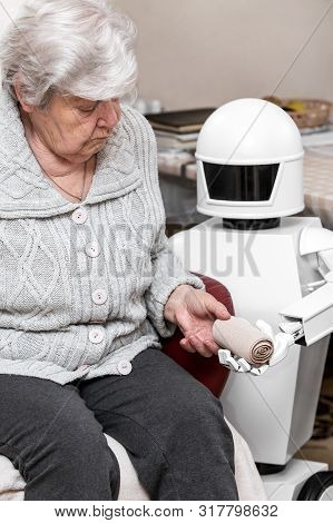 Autonomous Caregiver Robot Is Holding A Elastic Bandage, Giving It To An Senior Adult Woman In Her L