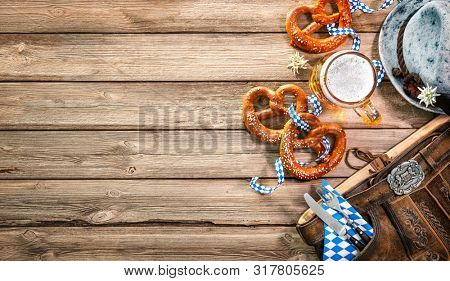 Background for Oktoberfest with Bavarian Lederhosen, hat, edelweiss, silverware, pretzels and beer stein on wooden tableHallo