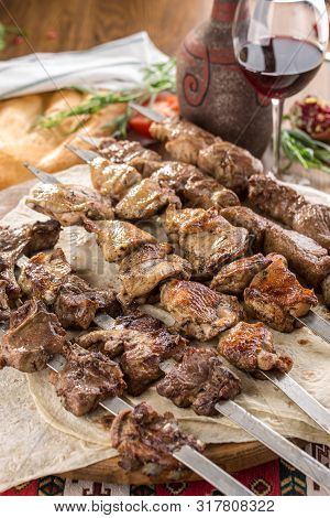 Lamb, Chicken And Pork Shish Kebab On Lavash Bread With Glass Of Red Wine On Wooden Table Side View