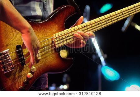 Professional Musician Plays Electrical Bass Guitar Solo On Concert Stage. Sring Musical Instrument O