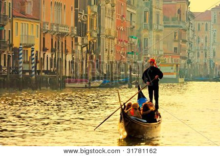 Gondolier navigates the venetian canal in sunset light