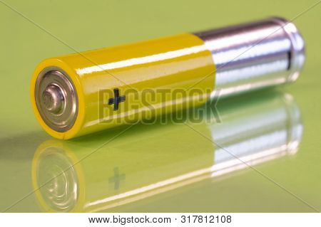 Single Aaa Battery Is Seen On A Reflective Green Surface. Closeup View From The Plus Side Of The Bat