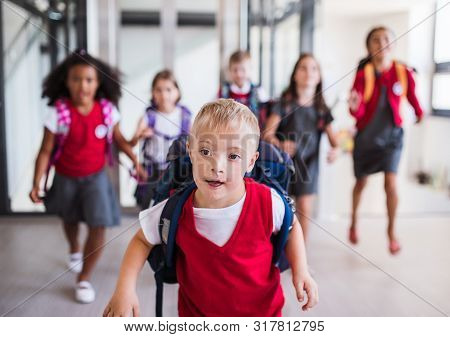 A Down-syndrome School Boy With Group Of Children In Corridor, Running.