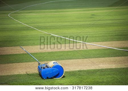 Cricket Roller By Boundary Edge Of Cricket Pitch On Sunny Day