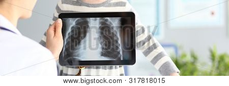 Female Doctor Examining Little Girl With Ultra Modern Scanning Tablet Pc Device Closeup