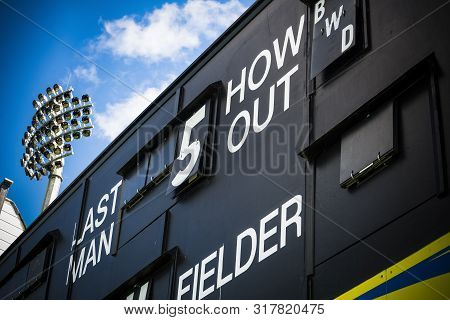 Cricket Scoreboard And Floodlight At Cricket Ground In Summer