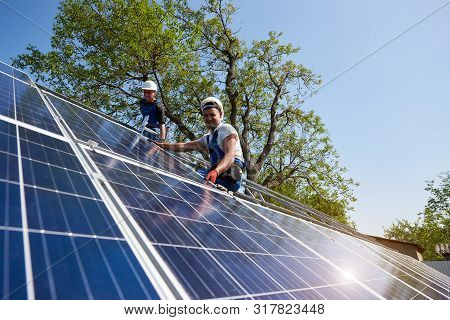 Two technicians sitting on metal platform installing heavy solar photo voltaic panel on blue sky and green tree background. Stand-alone solar panel system installation and professionalism concept. poster