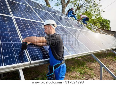 Professional engineer technicians installing exterior solar photo voltaic panel to metal platform on blue sky background. Stand-alone solar system installation, efficiency and professionalism concept. poster