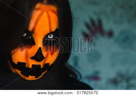 Spooky Bloody Pumpkin Face Of A Halloween Creature On Dark Background With Ritual Symbols. Close-up