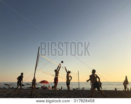 Beach Volleyball At Sunset By The Sea. Silhouettes Of Young People Who Play Volleyball On The Beach