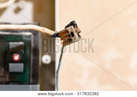 poster of Burned wire, splicing connector, electrical terminal block of nonflammable, fireproof material. Faulty wiring or negligent electrical work. Dangerous short circuit accident.