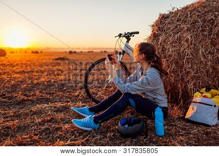 Young Bicyclist Having Rest After A Ride In Autumn Field At Sunset. Woman Taking Picture Using Phone