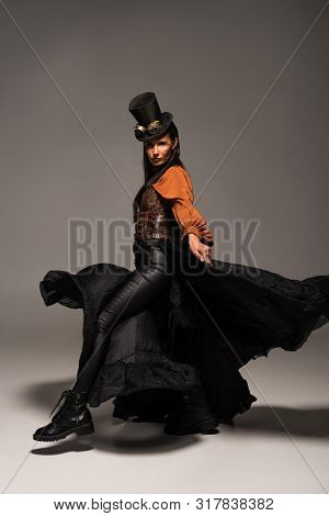 Full Length View Of Attractive Steampunk Woman In Top Hat With Goggles On Grey