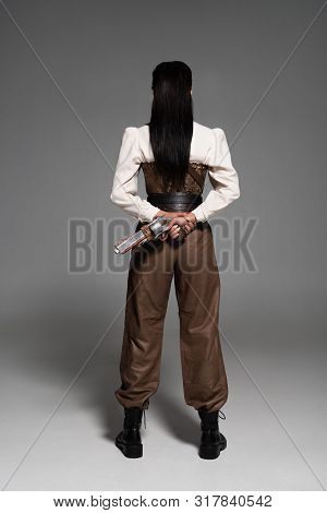 Full Length View Of Steampunk Woman Holding Vintage Pistol On Grey