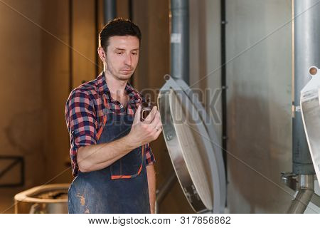 Middle Aged Caucasian Male Ceramist In Apron Inspects Quality Of Clay Pots After Firing In The Furna