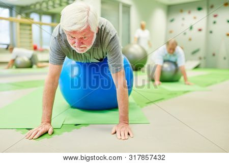 Senior does physiotherapy on exercise ball for back health and balance