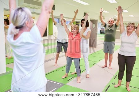 Group of seniors doing back exercises in physiotherapy under the guidance of rehabilitation trainers