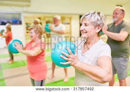 Senior group does back exercises with mini gym ball in physiotherapy