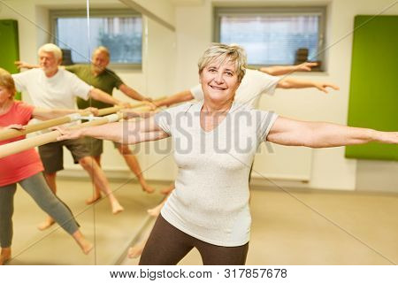 Vital senior makes rehab physiotherapy on the ballet bar in physiotherapy