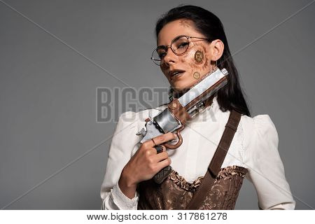 Pensive Attractive Steampunk Woman Holding Vintage Pistol Isolated On Grey