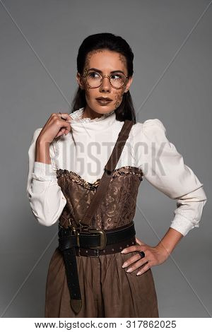 Front View Of Pensive Steampunk Woman With Makeup Looking Away Isolated On Grey