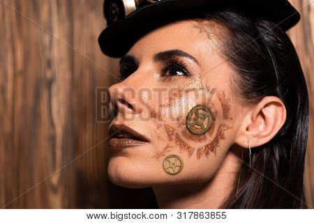 Pensive Attractive Young Woman With Steampunk Makeup Looking Up On Wooden