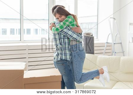 Young Couple Embraces And Dances In The Living Room Of Their New Apartment. The Concept Of Affordabl