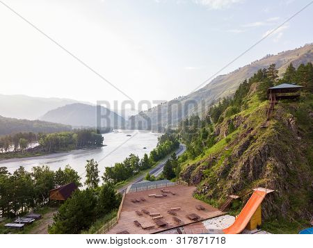 Outdoor Pool In The Altai Mountains With A Yellow Water Slide Attraction With Wooden Chaise-longue,