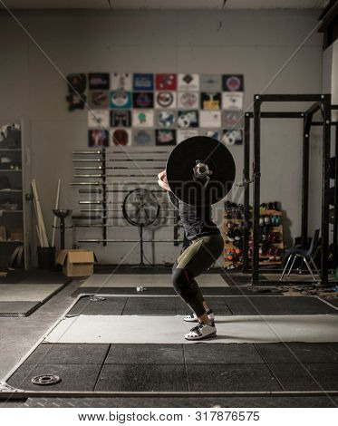 Female power lifter lifting heavy weights in dark gym, anonymous athlete.